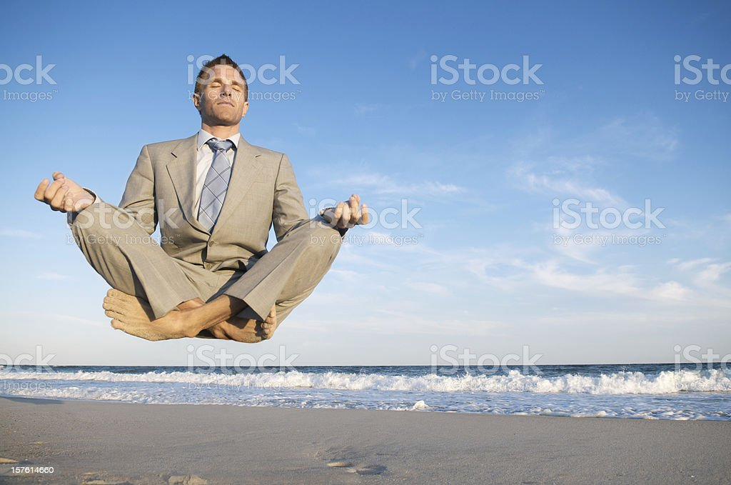 Peaceful Meditating Businessman Levitating Above Tranquil Beach stock photo