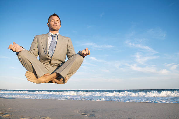 Peaceful Meditating Businessman Levitating Above Tranquil Beach stock photo