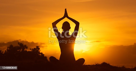 Woman meditating early morning in a beautiful outdoor setting.