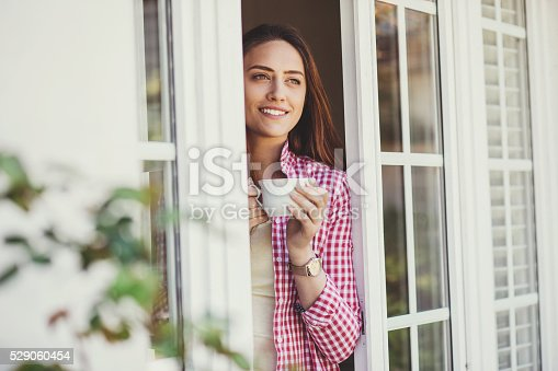 Beautiful young woman holding a cup of coffee looking through a house window. Shot made during Istockalypse Paris 2016 event.