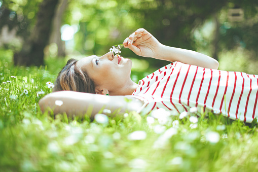 Smiling latin woman is lying down in the garden