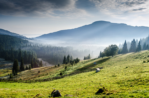 Morning rays and fog above a village in mountains.