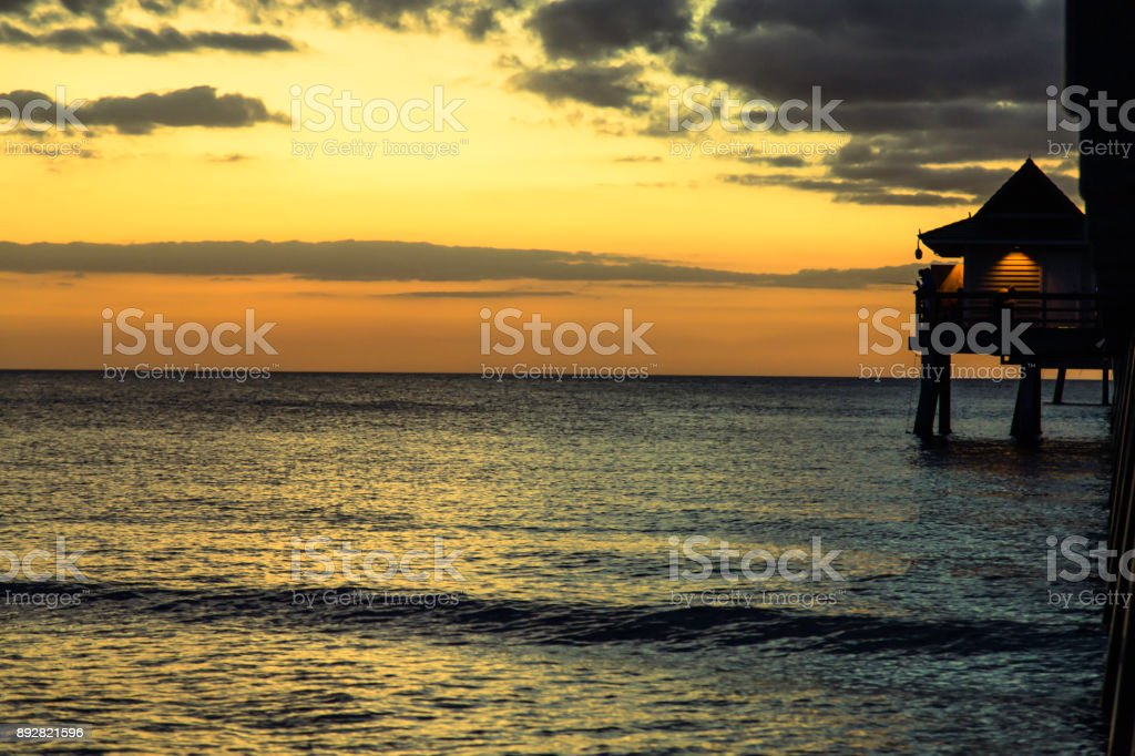 Peaceful Naples beach with pier stock photo