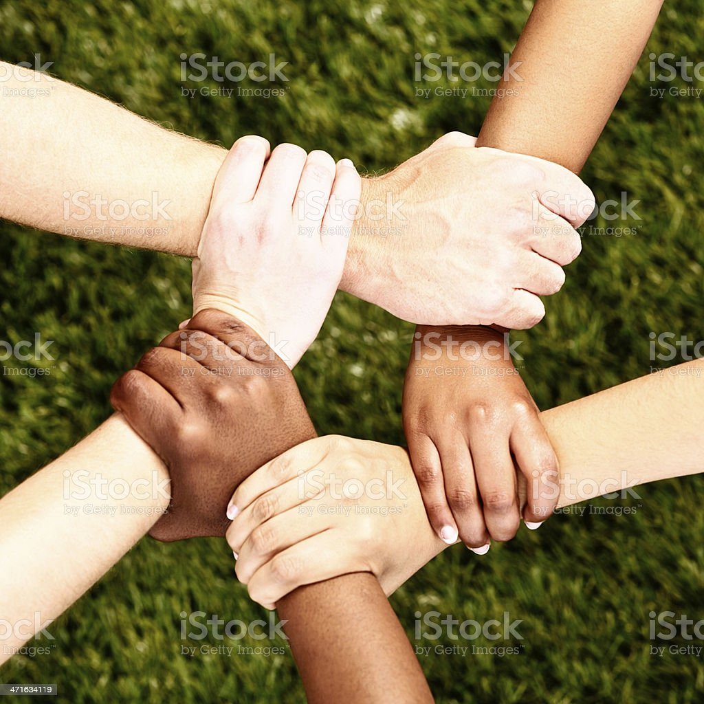 Peaceful pentagon: five clasped multi-ethnic hands on grass royalty-free stock photo