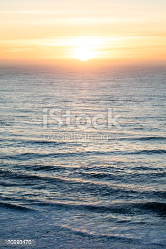 Beautiful sunset with sun setting over the pacific ocean water. Majestic scene with blue water and orange and yellow sky. Meditation, relaxation concepts.