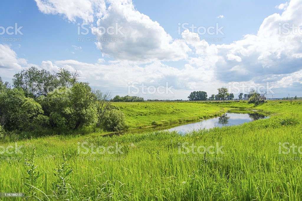 Peaceful rural landscape with river in wide field royalty-free stock photo