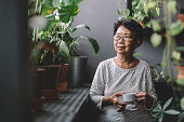 istock peaceful senior asian chinese woman having coffee at home chillling 1217962433
