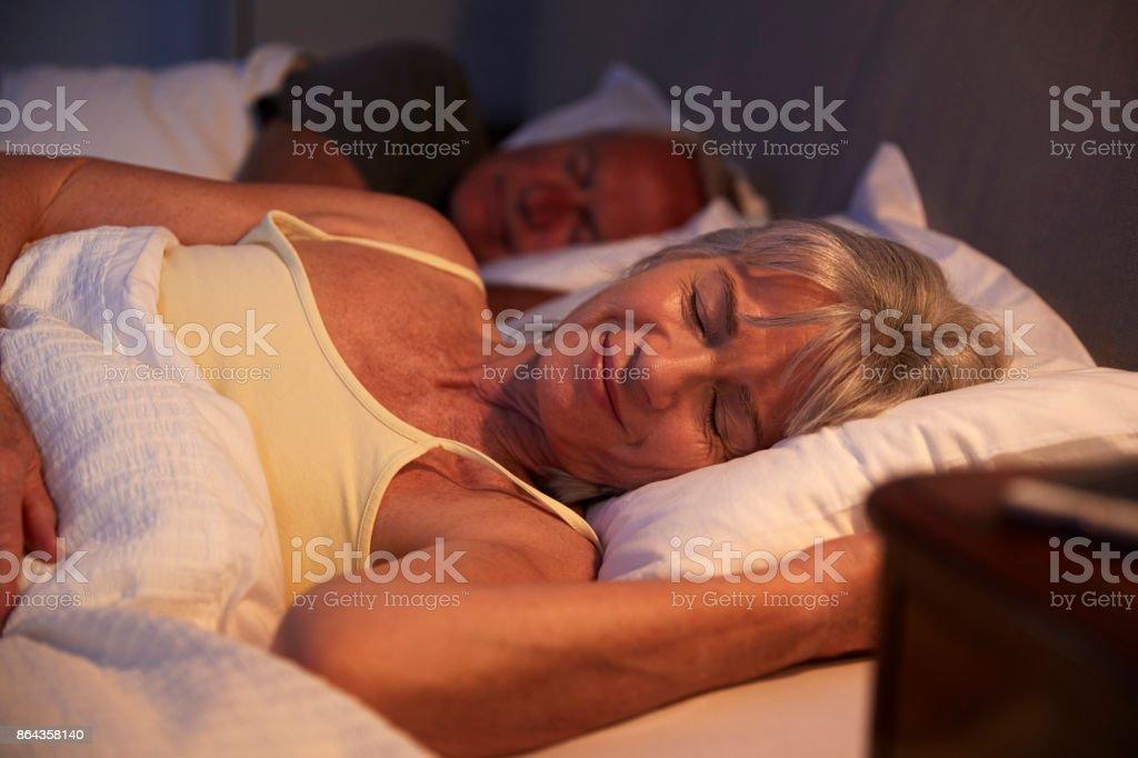Pacífica sênior mulher dormindo na cama à noite - foto de acervo