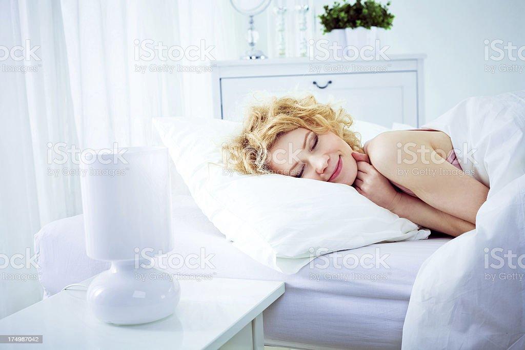 Peaceful sleep Happy young woman sleeping in white bedroom. 25-29 Years Stock Photo