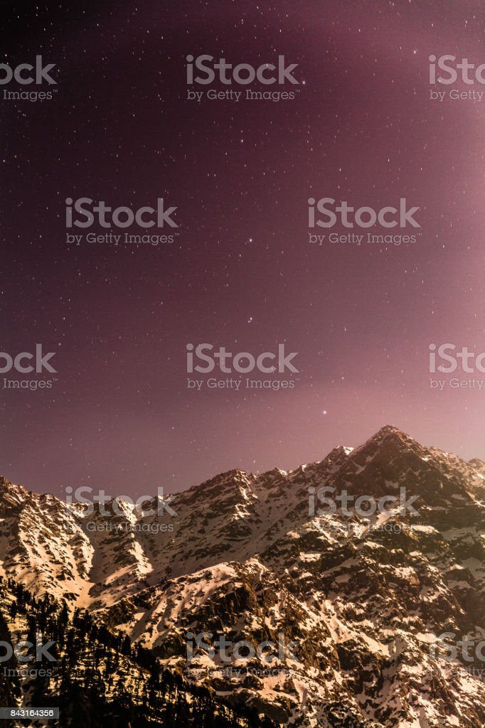 Peaceful starry night at Triund, Mcleod ganj, Dharamsala, himachal pradesh, India. Purple magenta skies with snow mountains in cold winter. Camping at night under the sky stock photo