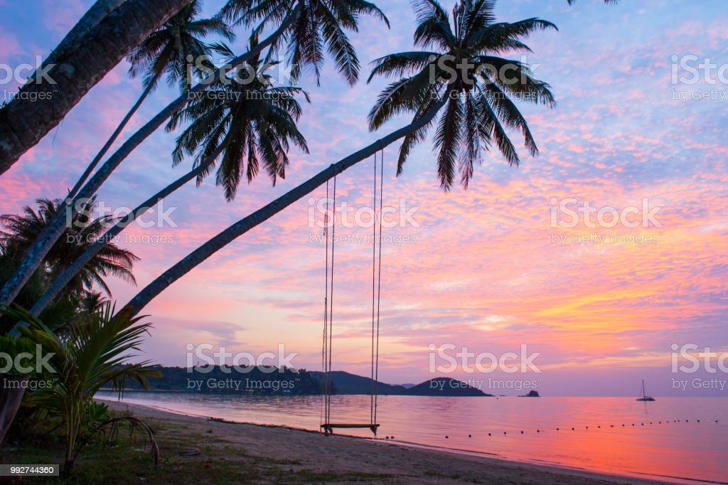 Peaceful time, beautiful clouds and sunset sky. Swing and coconut trees foreground, bay and yacht background. Summer season. Koh Mak Island, Trat, eastern Thailand. stock photo