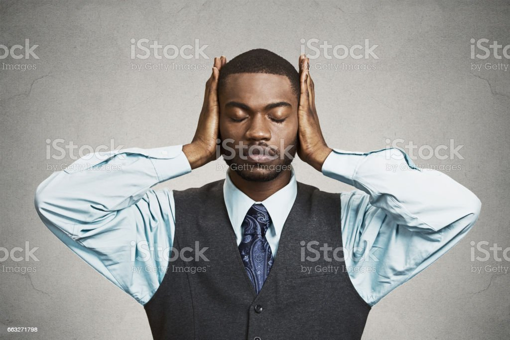 peaceful, tranquil, relaxed looking, young corporate business man covering his ears stock photo