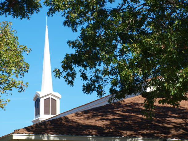 Peaceful View of Church Steeple Through Trees stock photo