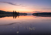 Peaceful view with sunset, lake and standing water at summer night in Finland.