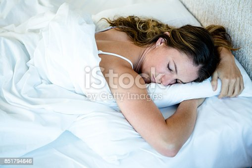 peaceful woman asleep in her bed, lying on her stomach