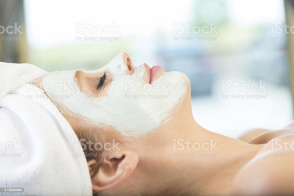 Peaceful woman relaxing during facial at tranquil spa stock photo
