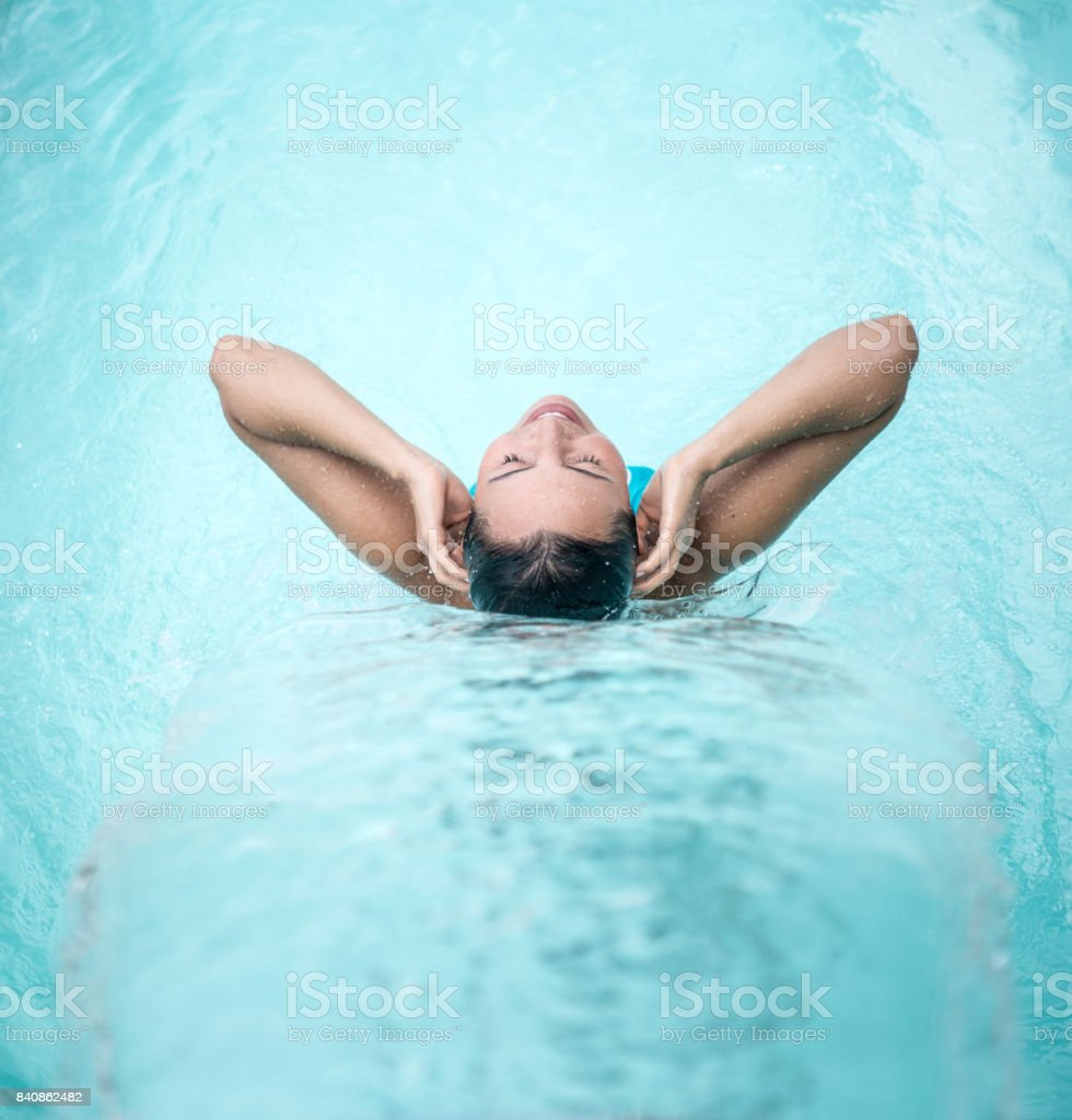 Peaceful woman relaxing under a waterfall at the spa stock photo