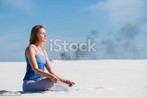 istock Peaceful woman sit in lotus yoga pose 1039188720