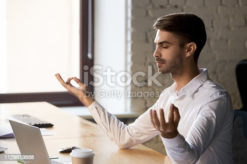 916520034istockphoto Peaceful worker meditating with eyes closed at office table 1129819888