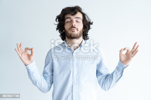 istock Peaceful young man meditating with his eyes closed 992667746