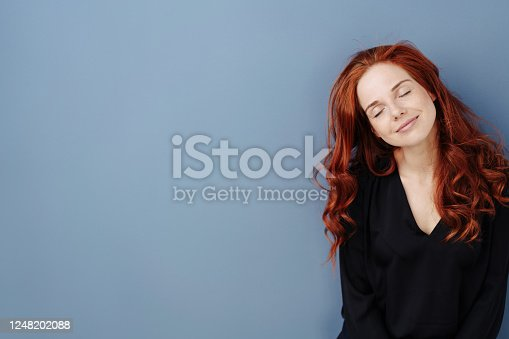 Peaceful young woman taking a moment to relax standing with eyes closed and head titled smiling happily to herself over a blue studio background with copy space