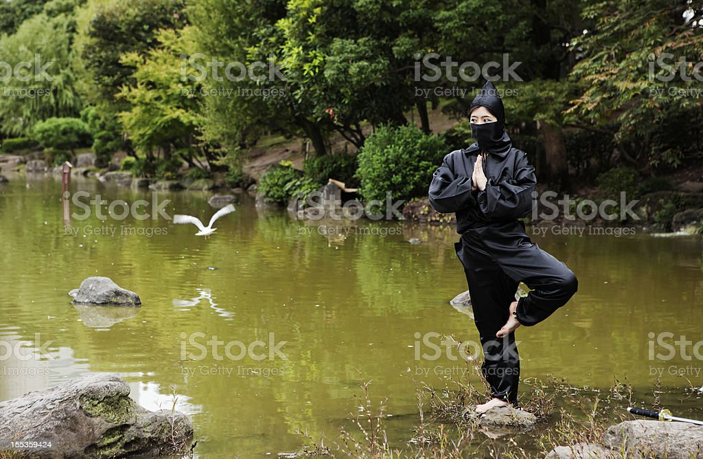 Peacefull Ninja meditating on a stone in a lake, Japan royalty-free stock photo