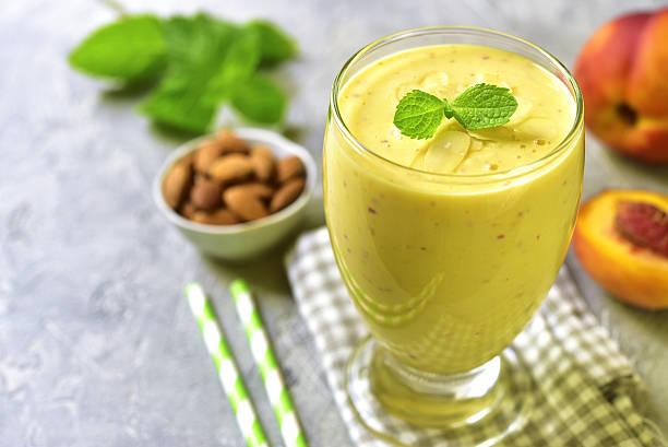 peach and banana smoothie with almond.space for text. - pfirsich milchshake stock-fotos und bilder
