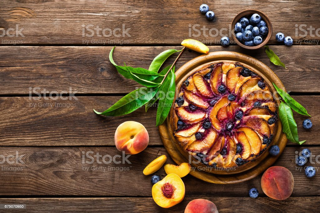 Peach cheese cake or pie with fresh blueberry on wooden rustic background, top view, closeup stock photo