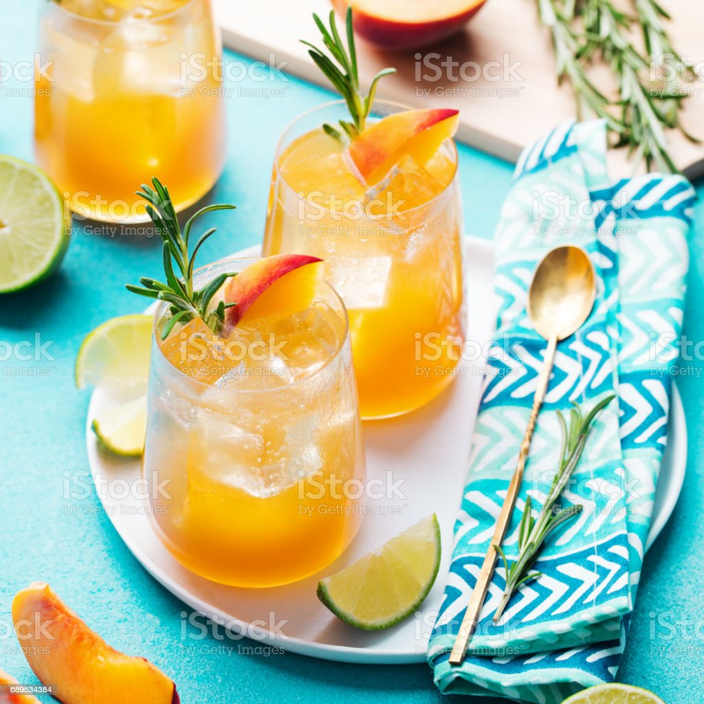 Peach cocktail, fizz, ice tea with fresh rosemary and lime. Blue background. stock photo