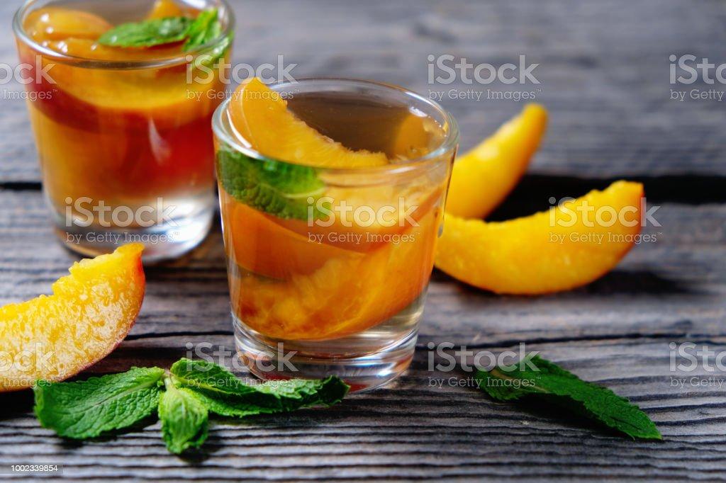 Pfirsich-cocktail oder Tee mit Minze auf hölzernen Hintergrund. – Foto