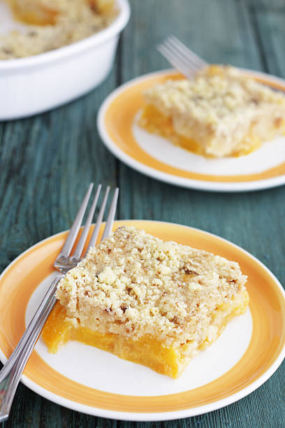 Peach crumble served on yellow dish on green table stock photo
