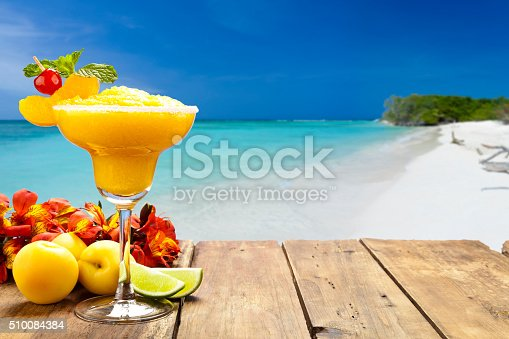 Peach daiquiri on wood table against tropical beach background. The glass is placed at the left of the frame leaving a useful copy space at the center-right