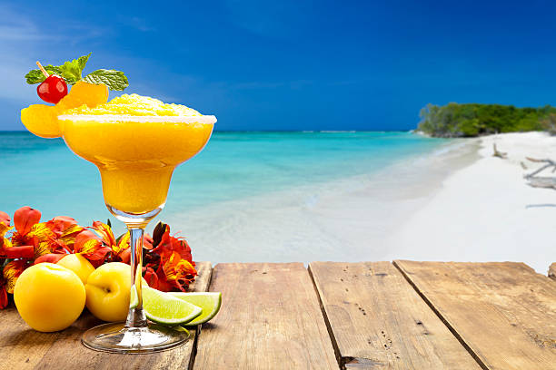 peach daiquiri on wood table against tropical beach background - margarita drink stock photos and pictures