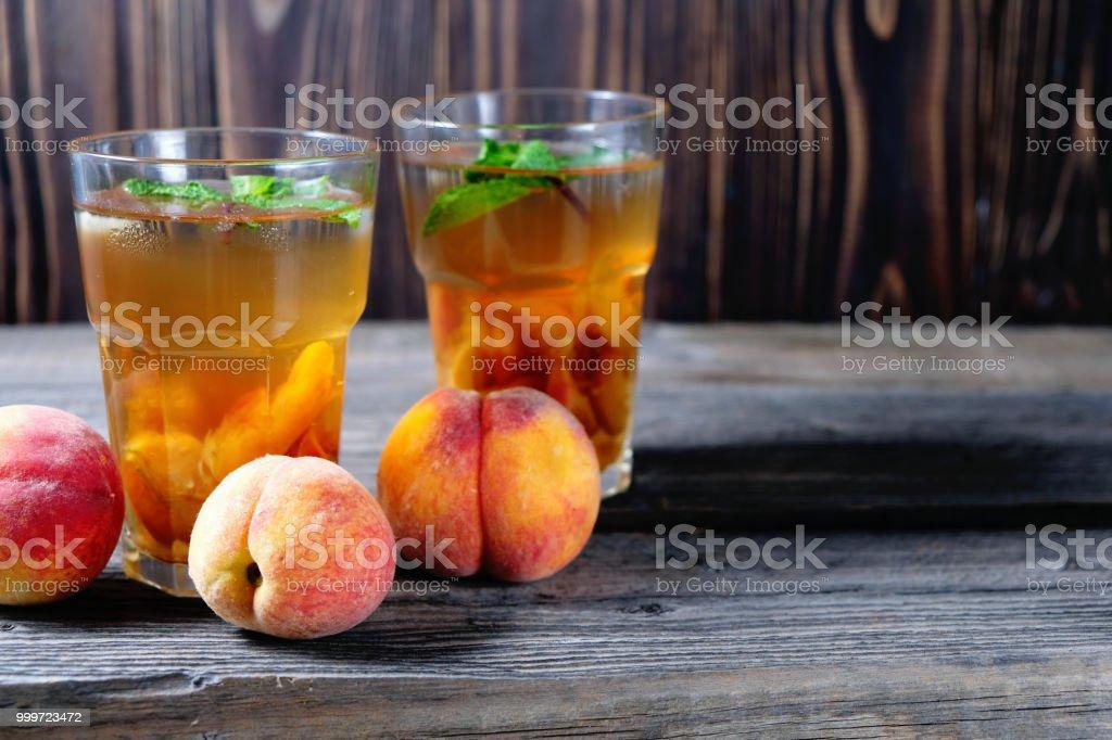 Pfirsich Eistee in ein Glas mit Minze auf Holztisch – Foto