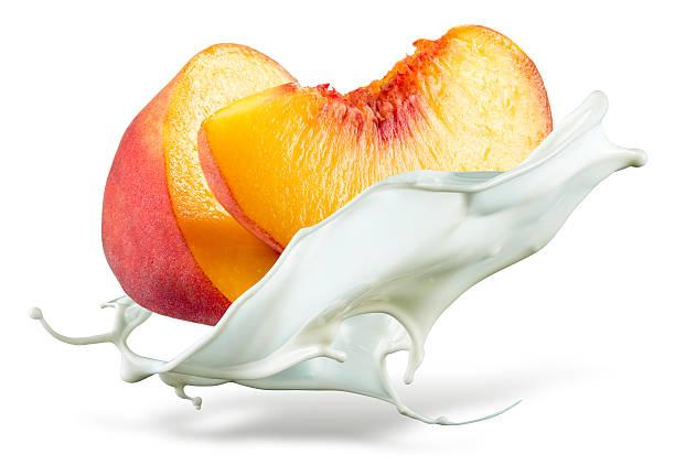 peach ist fallen in der milch. splash isoliert auf weißem hintergrund - pfirsich milchshake stock-fotos und bilder