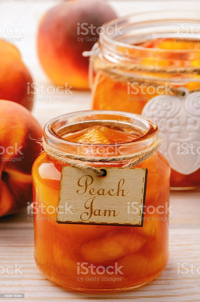 Peach jam in glass jars on white wooden background. stock photo