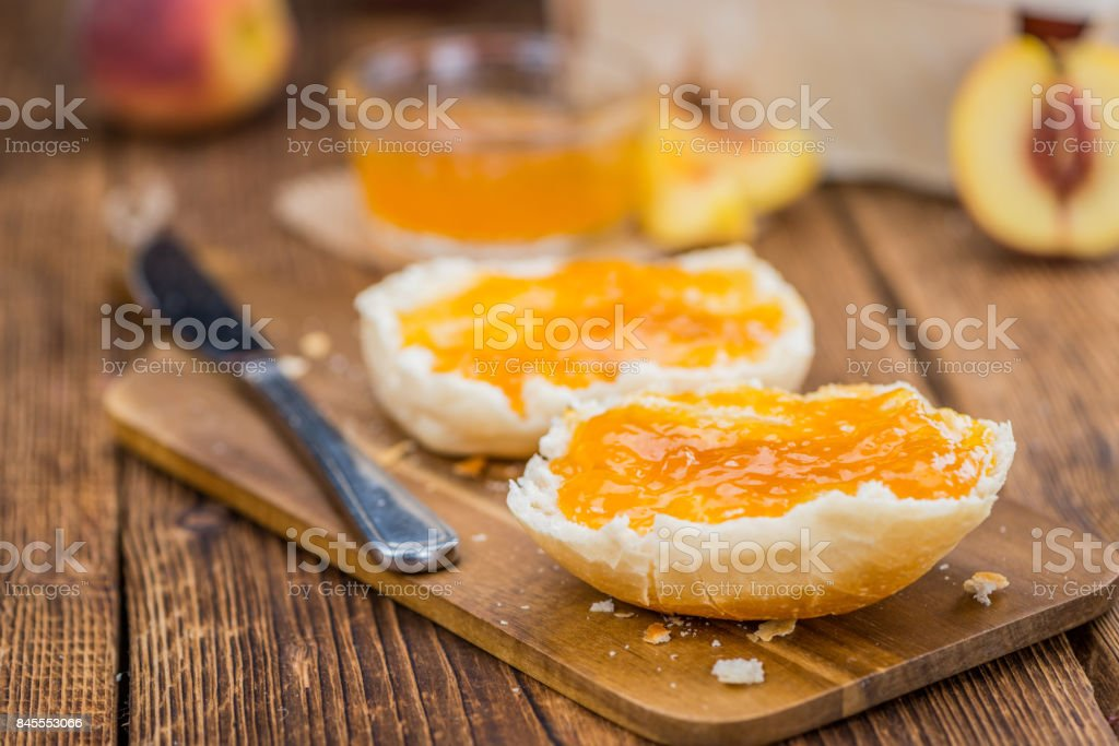 Peach Jam on wooden background; selective focus stock photo