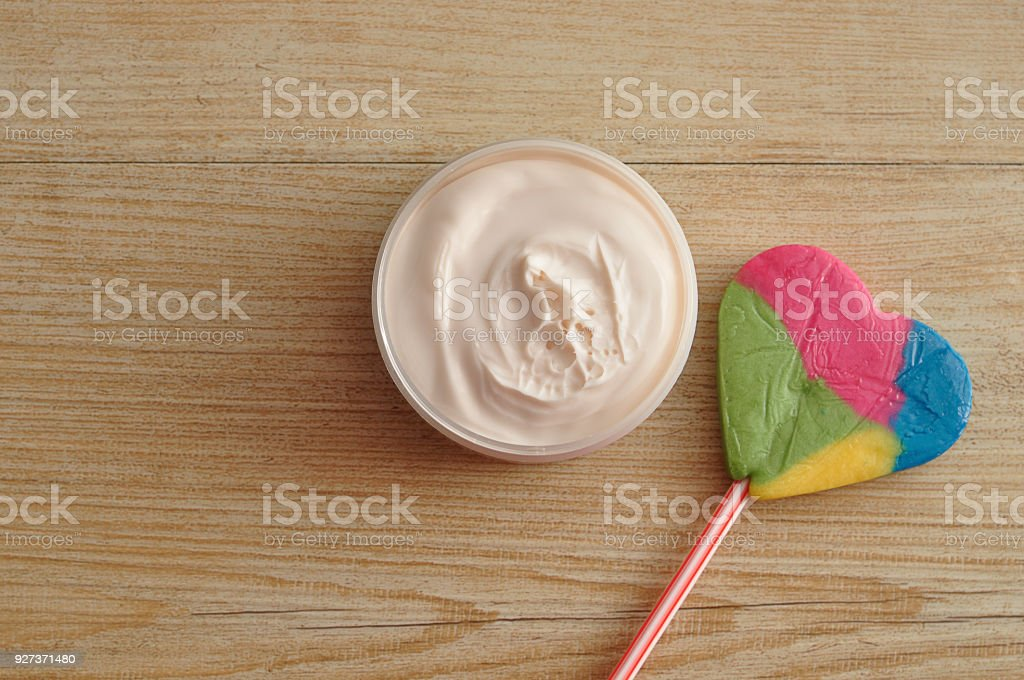 A peach jar of body lotion displayed with a heart shape lollipop - Royalty-free Aging Process Stock Photo
