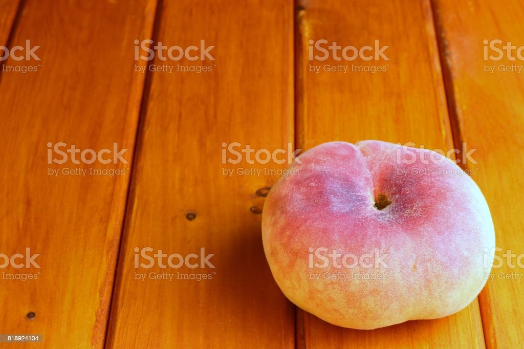 A peach on a wooden surface stock photo