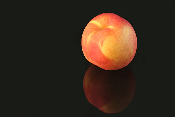 Peach on black reflecting surface stock photo