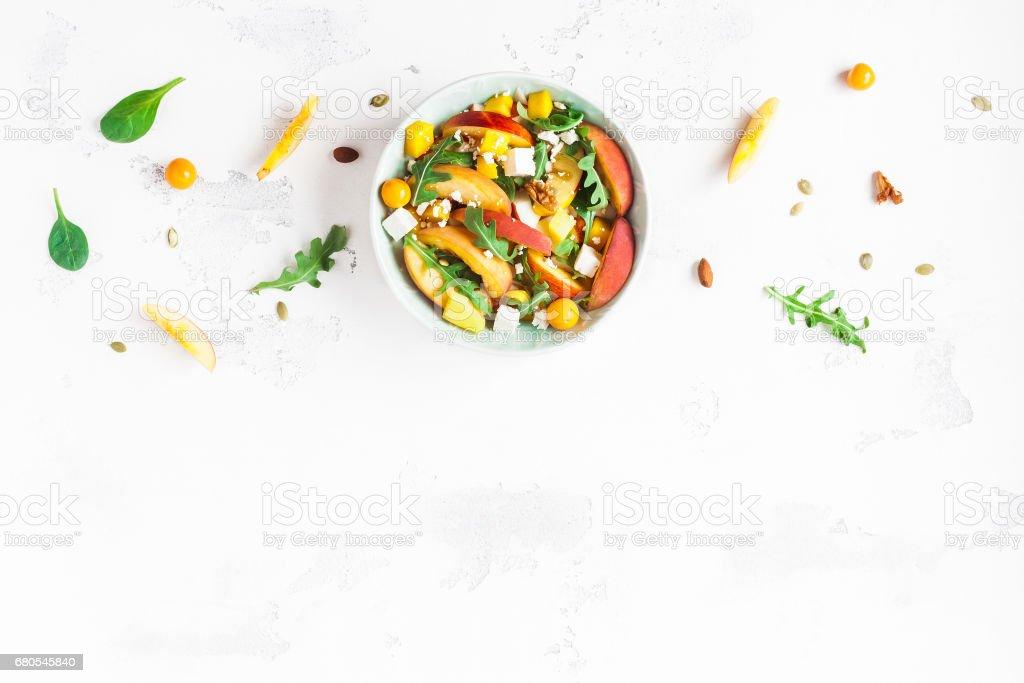 Peach salad. Spinach leaves, arugula, sliced peaches, mango, nuts, cheese stock photo