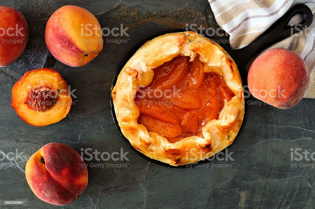 Peach tart in cast iron skillet, scene over slate stock photo