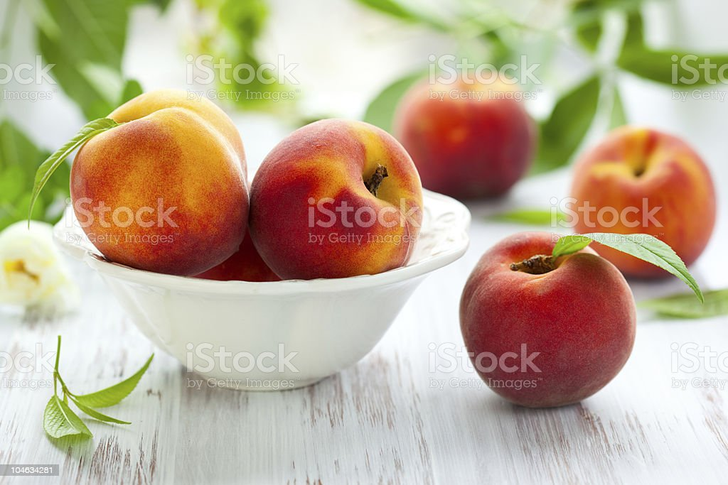 Peaches in bowl and on the table stock photo