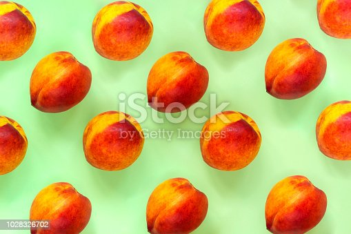 Peaches pattern. Top view of fresh fruits on a green background