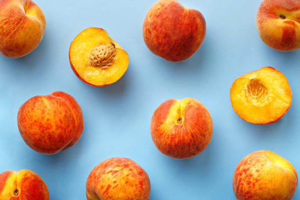 桃子模式。藍色背景上的新鮮水果的俯視圖。重複的概念 - 桃 個照片及圖片檔