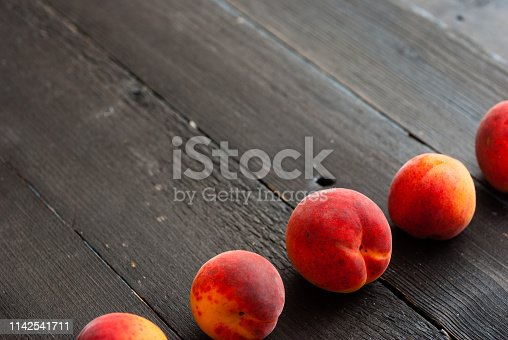 whole peaches in a row on black wood table