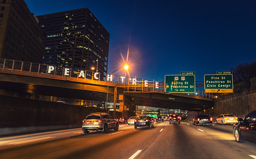The lit Peachtree sign on the bridge identifying Peachtree Street from afar.