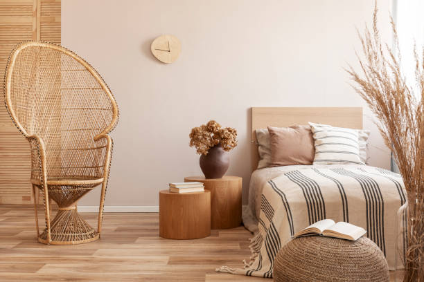 Peacock chair next to single bed with beige bedding and warm blanket, real photo stock photo