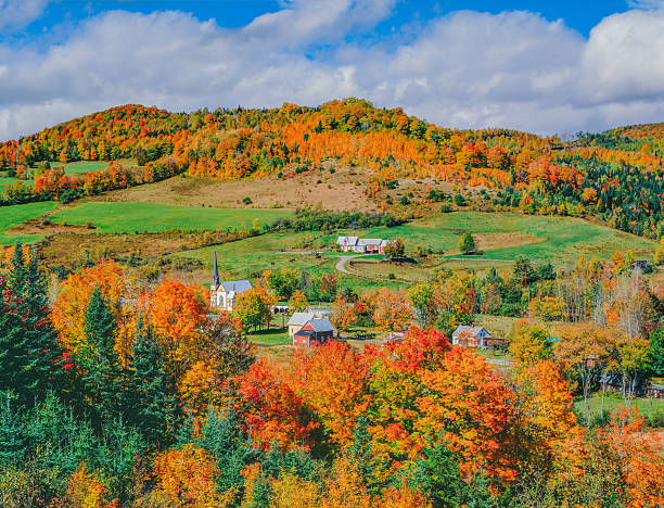 Peak autumn sugar maples with village in Vermont Quaint New England Village of East Orange with peak autumn color, Vermont appalachian trail stock pictures, royalty-free photos & images