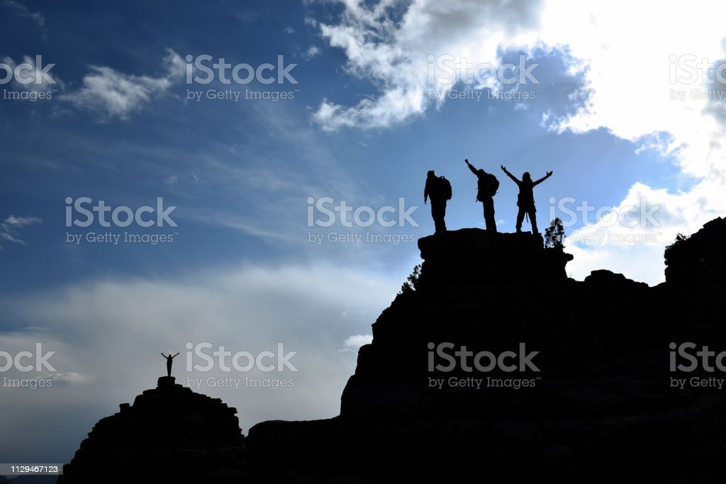 peak success of happy and enthusiastic mountaineers stock photo